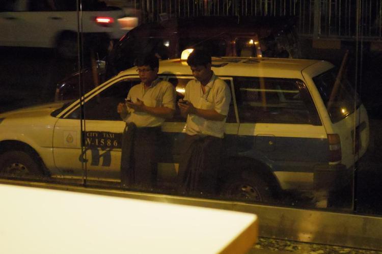 ロンジー姿のタクシードライバーも仕事そっちのけでスマホいじりに精を出す